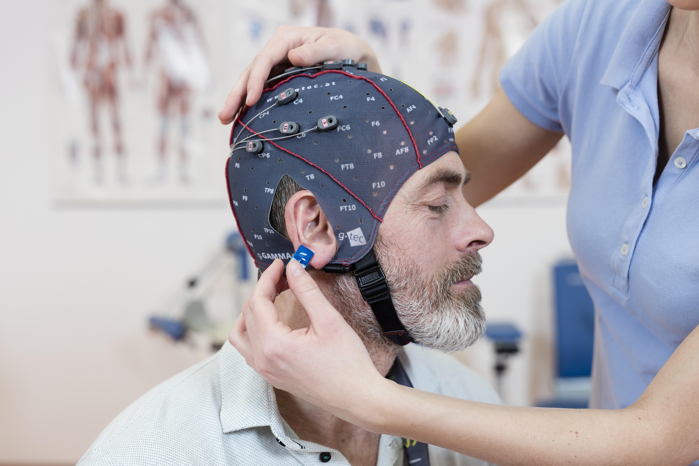 Miehen päässä on RecoveriX-aivokuntoutukseen kuuluva elektrodimyssy.